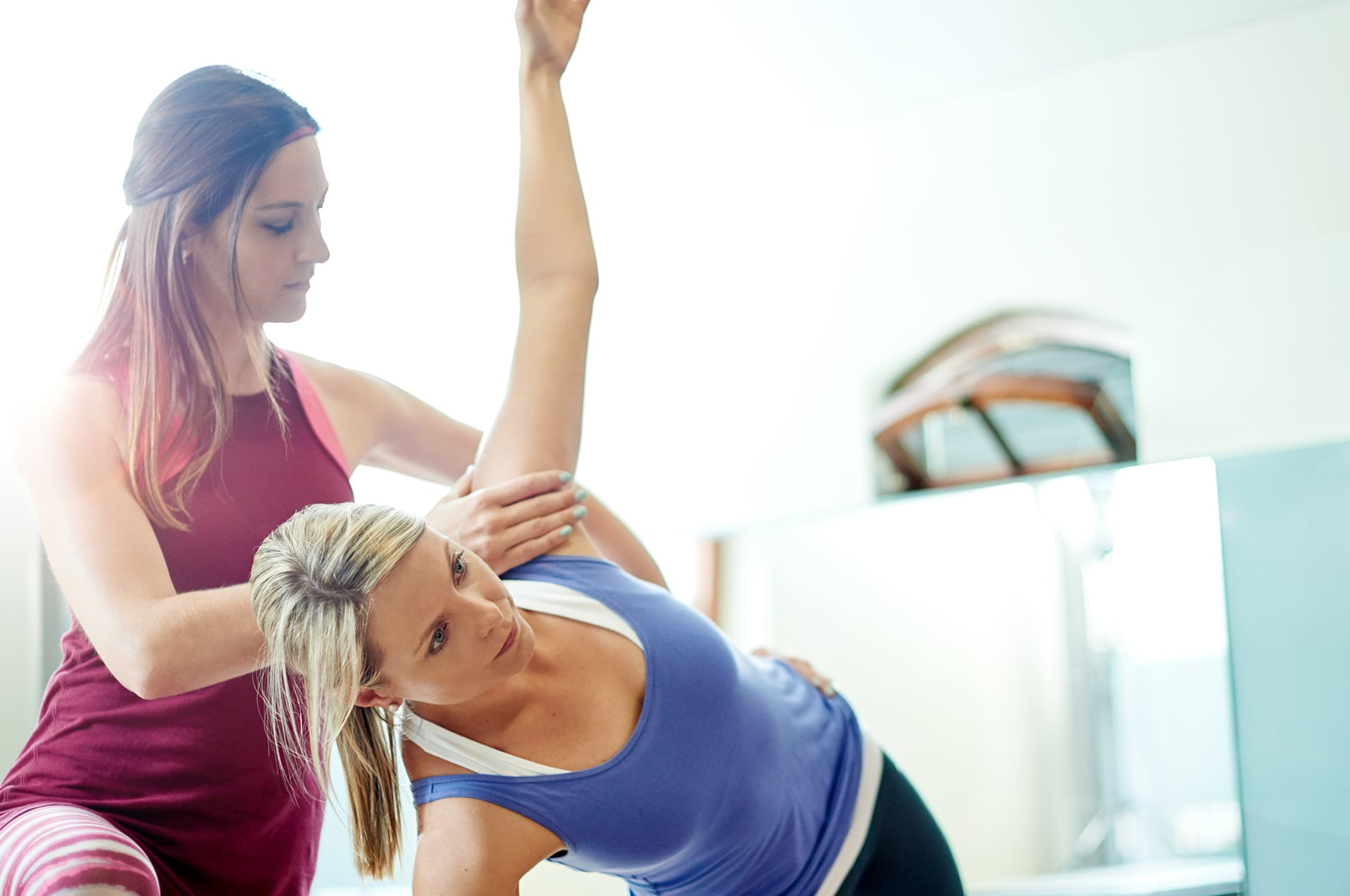 One woman helping another woman with side yoga pose