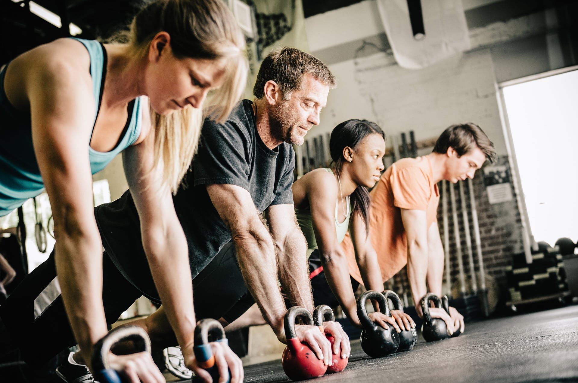 Group of people planking on kettle bells in studio