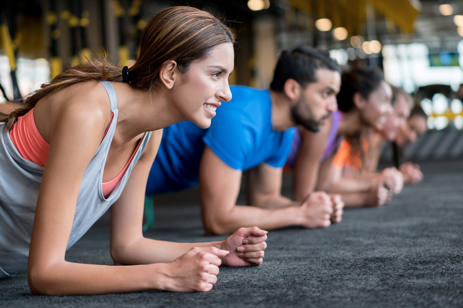 Diverse group of people plank in a gym class studio