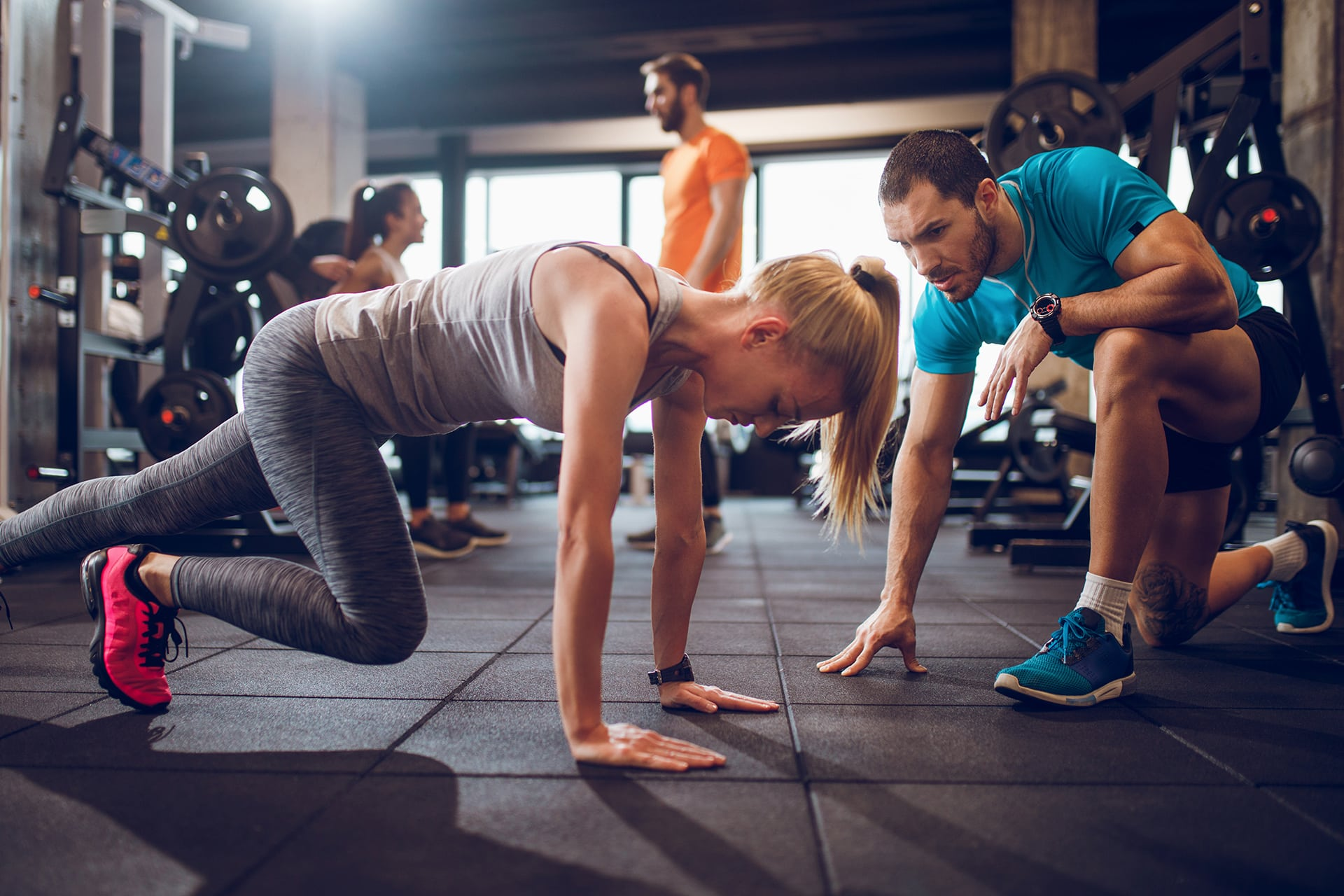 Male personal trainer encourages woman while she exercises
