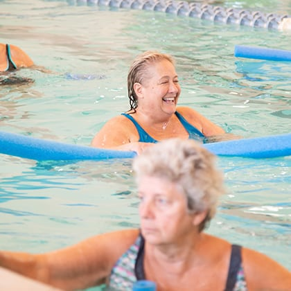 Senior woman laughing in pool with pool noodle