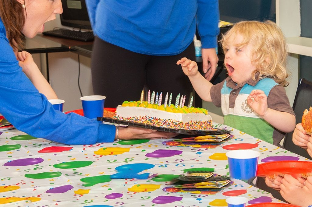 Little Boy Blowing Out Candles On Birthday Cake
