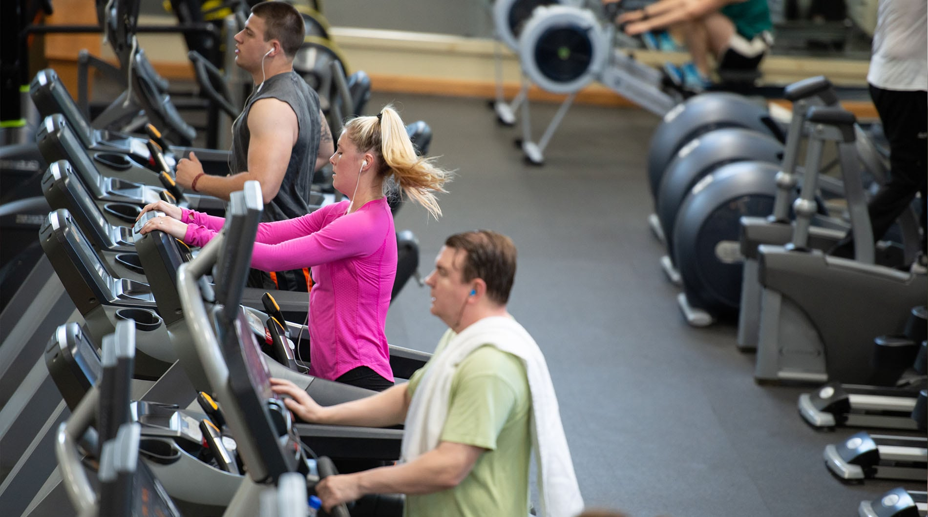 group of fit people running on treadmills