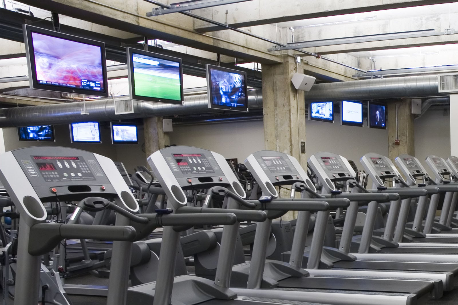 row of empty treadmills with TV stations above