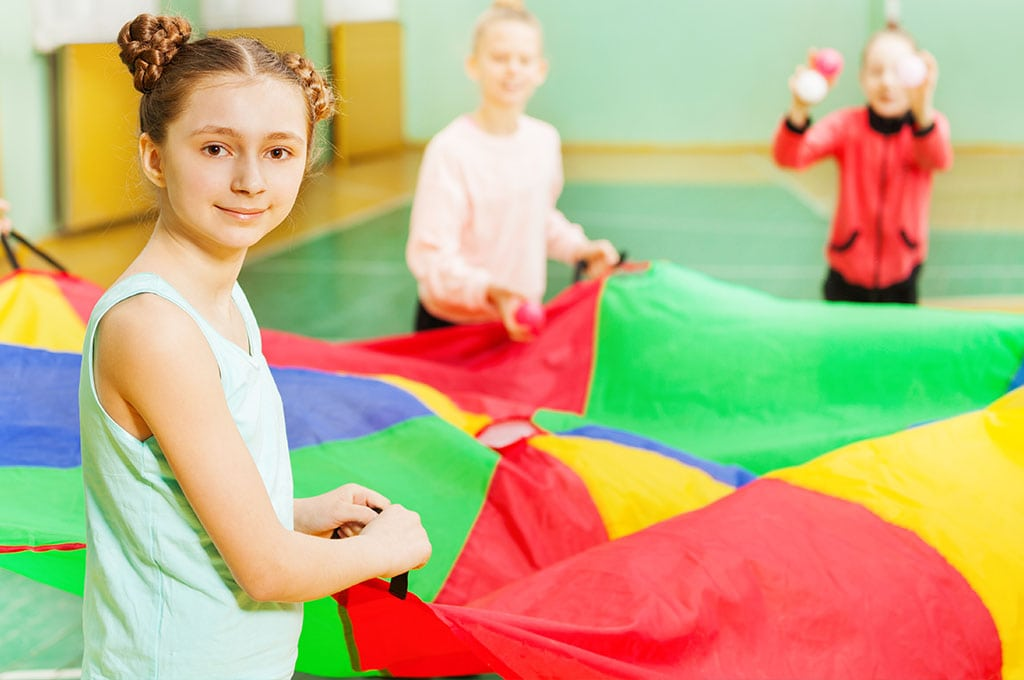 girl with braids smiling,, holding a parachute with friends in a gymnasium