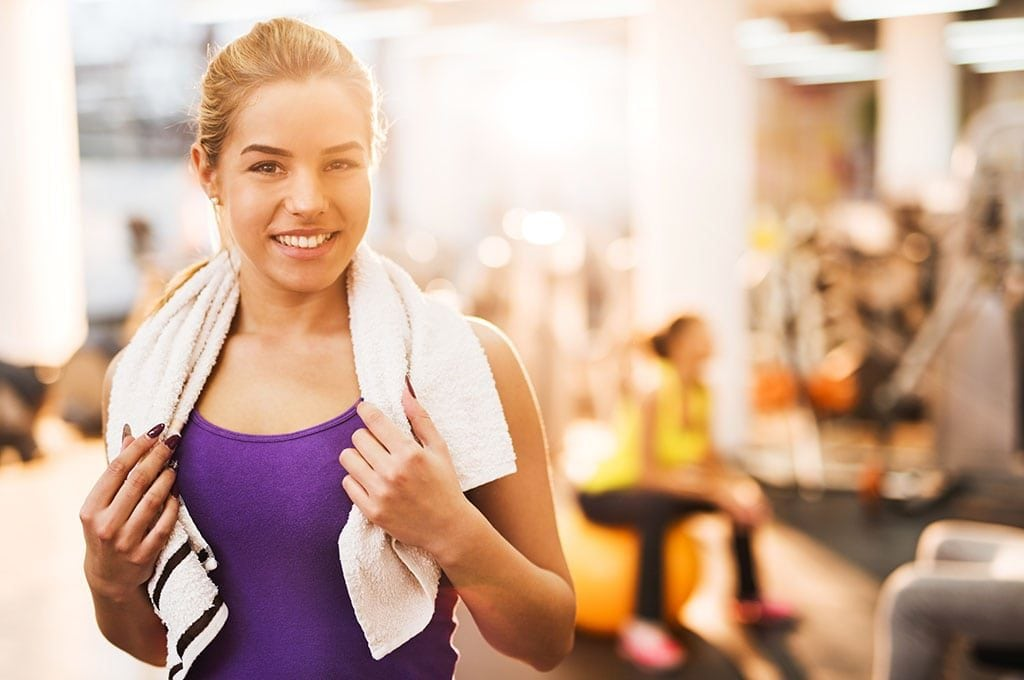 fit woman smiling in gym