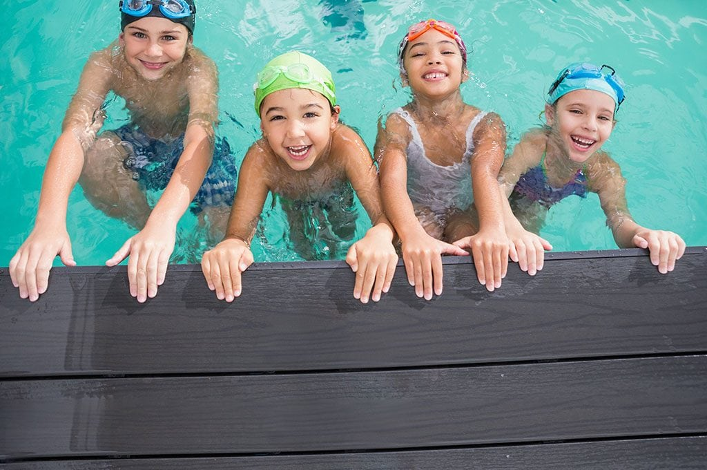 children smiling and holding onto the side of a pool