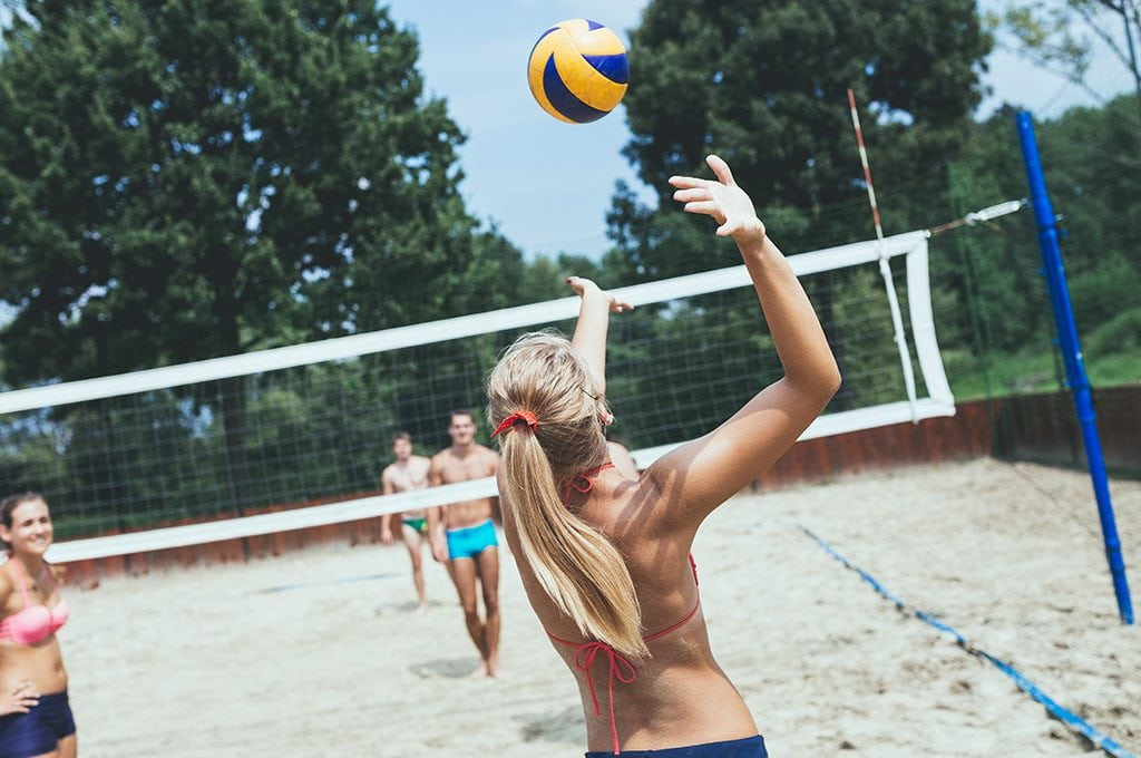 woman serving a volleyball on a sand volleyball court