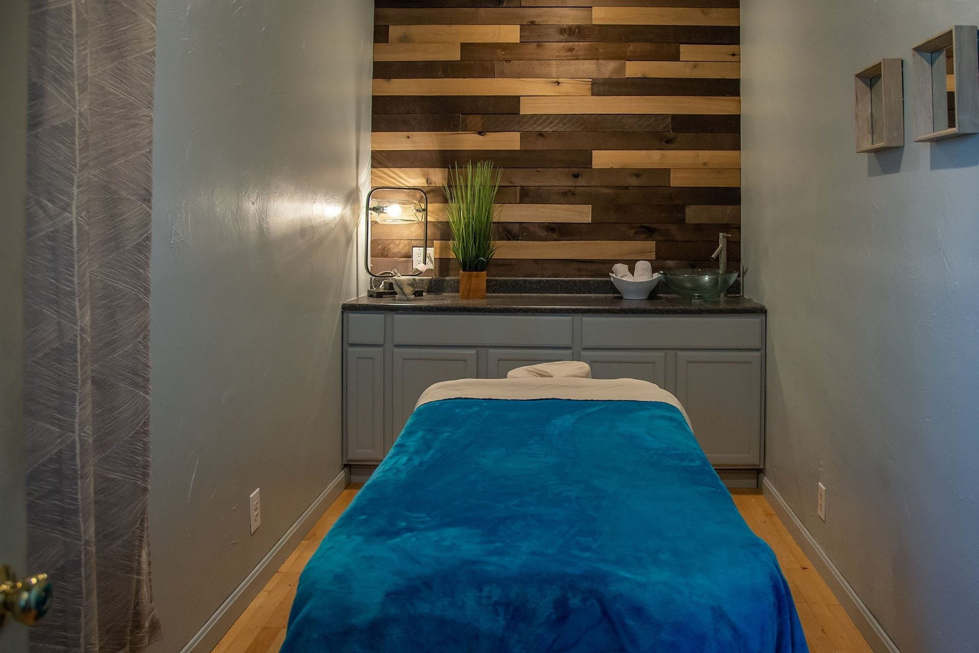 serence massage room with bamboo wall and blue velvet massage table