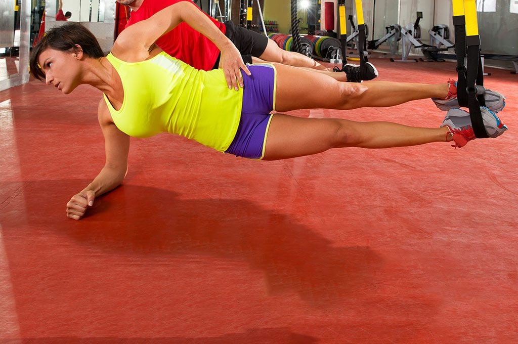 fit woman with feet in TRX bands, on side