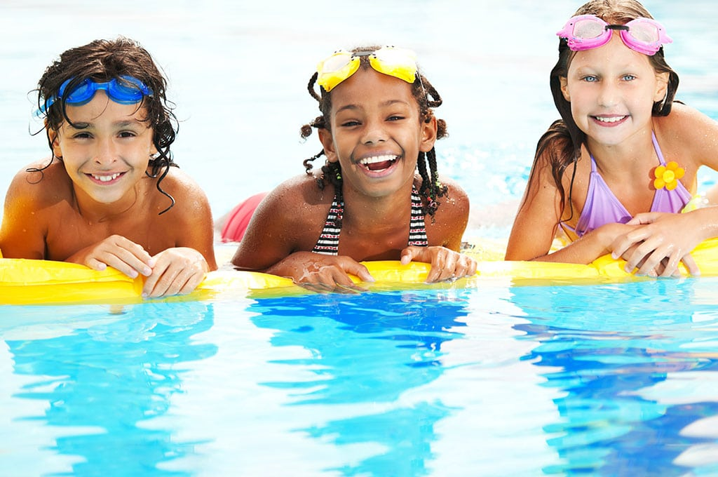3 kids in pool, smiling. floating on a yellow raft